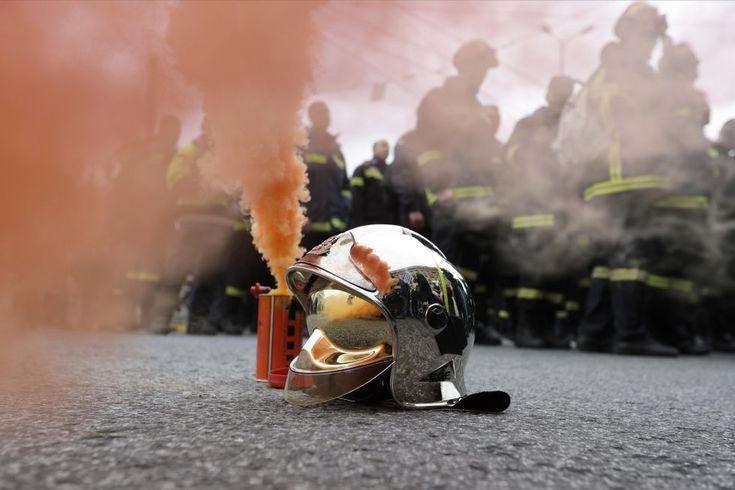 Un casco de bombero al lado de una bengala durante una manifestación en el centro de Atenas (Grecia). Cientos de bomberos en uniforme han tomado las calles de la capital griega en protesta por las condiciones de contratación.
