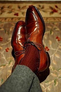 Burgundy socks, brown shoes. grey trousers.