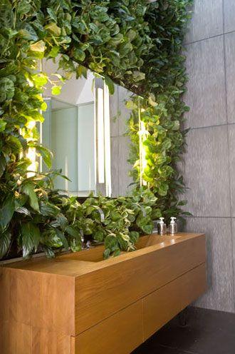 Vertical Garden With Artificial Plants Around Bathroom Mirror