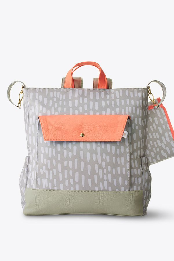 Sometimes you need two free hands when you're out and about with Baby. That's where the Oh Joy! Backpack Diaper Bag comes in. The muted gray print with peach accents is both attractive and versatile. Whether you carry the bag on your back or by its handle, or use the stroller strap, you'll find it offers style and convenience when you pack up diapers, wipes, bottles and toys for Baby, as well as a few things for you. Don't forget to add it to your registry, because you'll need it soon!