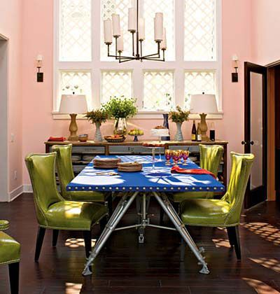The red-orange tinted walls, the yellow-green chairs, and the vibrant blue-violet table top create a triadic color scheme.