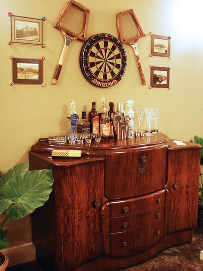 Antique walnut bar cabinet from the 1920s has pull out drawers & hinged bookcase sides. Looks right at home with sports theme decor.