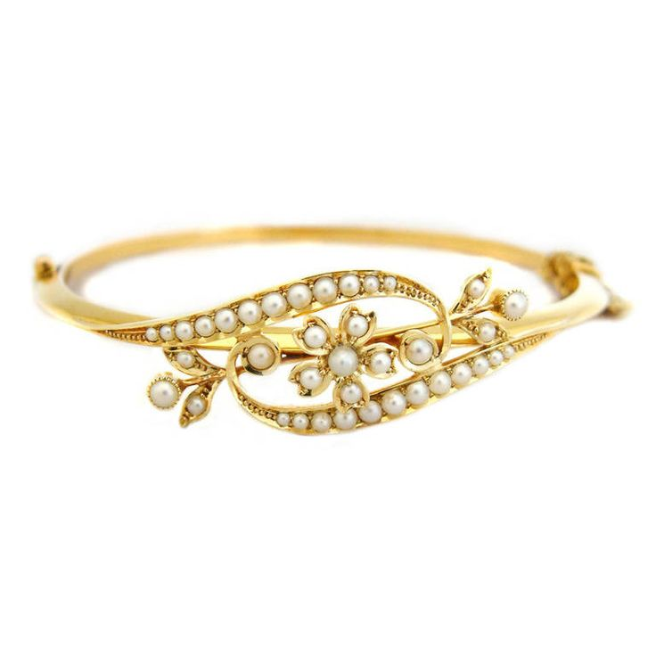 Antique Victorian Pearl Gold Bangle. An antique 15ct gold hinged bangle from the Victorian period, comprising a floral motif set with half pearls to the front. Fitted with a secure clasp in full working order.