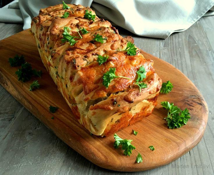 ForestilJer et lunt, nybagt brød, som man kan trække fra hinanden imundrette bidder– hvidløgsduftende og fyldt med lommer af letsmeltet ost – en blanding af cheddar og mozzarella som laver lange strenge, når man hiver en luns af brødet. Sådan et brød – altså et pull apart brød med ost og hvidløg –spiste vi til …