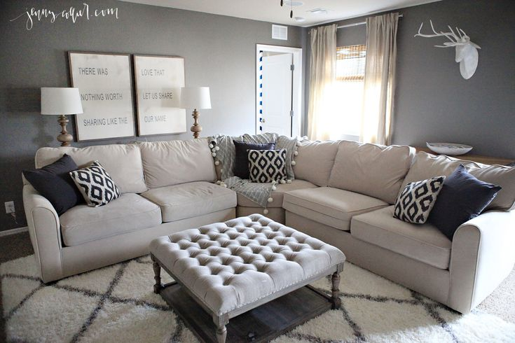 Neutral Living Room with Chelsea Gray walls, a cream sectional, Morrocan rug, Between You and Me signs, tufted ottoman, pom pom throw, and linen pillows.