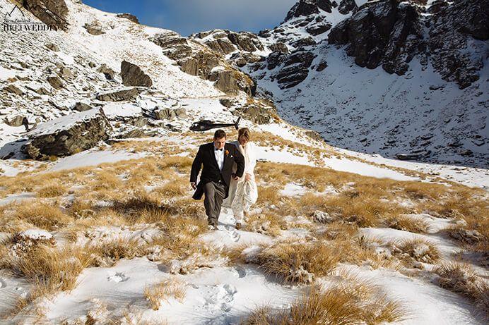 Bride and groom walking in snow on destination wedding in Queenstown, New Zealand