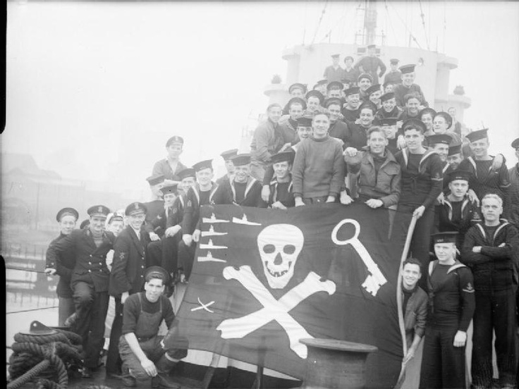 Men from all frigates of the 21st Escort Group of Captain Class Frigates with their Jolly Roger on board HMS CONN after returning from a patrol in which they sank three U-Boats and a possible fourth. Five U-boats is the group's total of kills. Crossed scalpels at the bottom indicate two surgical operations performed at sea during patrols.