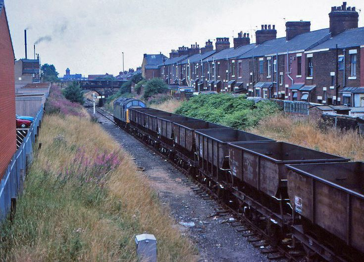 40002 plods along the former Preston to Longridge branch, running between Porter Street and Deepdale Road with a rake of empty 21 Ton Coal Hoppers returning from Fletcher Road sidings to Healey Mills on a dull and overcast August 15th 1983. The loco is passing through the site of Deepdale Station closed in 1930 when regular passenger trains were withdrawn by the LMS between Preston and Longridge. 40002 was new from Vulcan Foundry in April 1958 and was withdrawn after 26 years service in May…