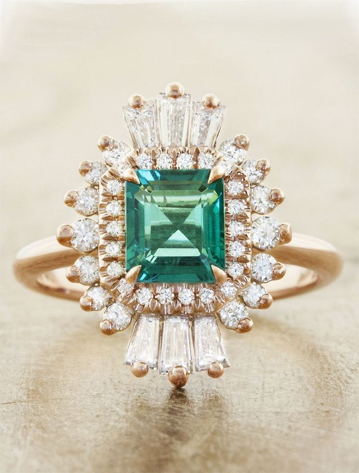 Caldonia features a halo of shooting stars created by 0.882 tcw diamonds surrounding a roaring green emerald, inspired by art deco designs.