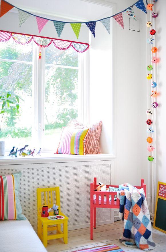 guirlandes colorées sur murs blancs, coussins rayés et meubles peints pour une belle chambre d'enfant