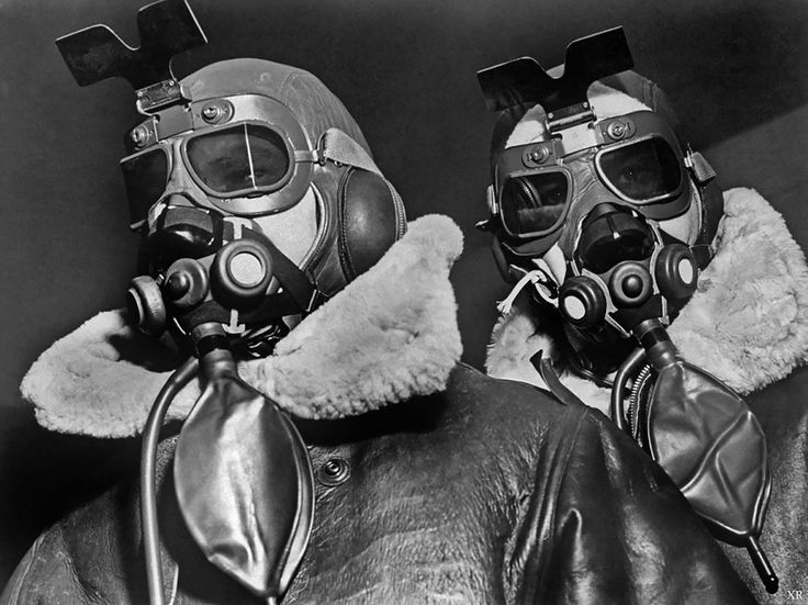 Two fliers of the 8th Bomber Command clad in high altitude flying clothes including sheepskin coats & helmets, oxygen masks and sunglass goggles, at airdrome in southern England.