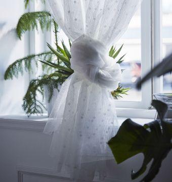 Primer Plano de una cortina blanca atada en la parte inferior.