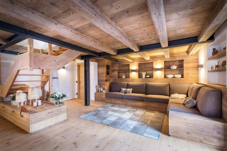 Domina il soggiorno un grande divano angolare rivestito in tessuto in una tinta naturale che riprende le nuance delle tavole del legno d'abete della boiserie, del pavimento e del soffitto a travi.