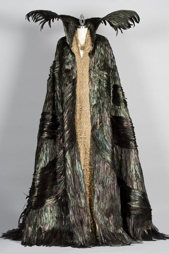 Snow White and the Huntsman, 2012  Costume design: Colleen Atwood    raven feather cape worn over a three-patterned gold embroidered dress - worn by Charlize Theron in the role of Queen Ravenna