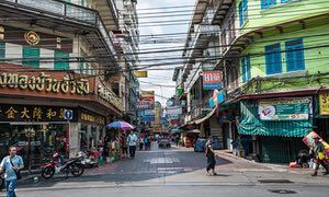 Daytime shot of a people crossing a street in Chinatown, Bangkok, Thailand