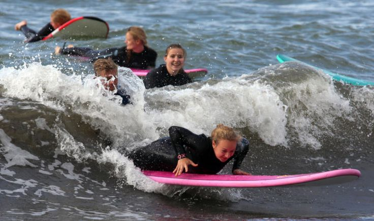"""Am Ostseestrand von Rostock-Warnemünde (Mecklenburg-Vorpommern) starten die Teilnehmer eines Surfkurses ihre ersten Versuche im Wasser. Die """"Surfschule mit Wellengarantie"""" nutzt für ihre Kurse vor allem auch die Wellen der Scandlines-Fähren, die alle zwei Stunden den Rostocker Hafen anlaufen."""