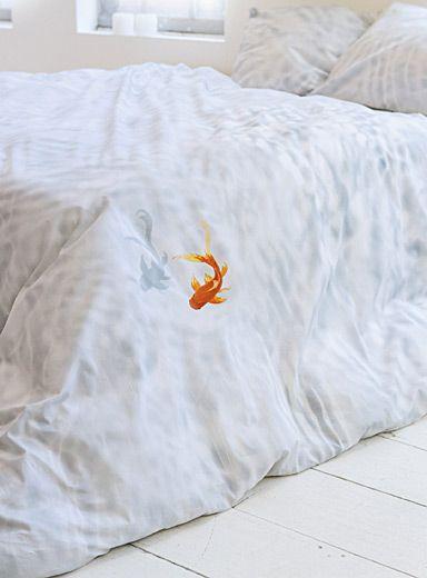 Collection Snurk d'Amsterdam chez Simons Maison.  Après avoir passé 25 ans dans un étang, le petit poisson rouge Bassie a décidé de s'installer sur cette housse de couette ! Et quel choix judicieux : une eau cristalline et un doux coton de qualité supérieur. Qui n'y serait pas heureux comme un poisson dans l'eau ?      L'ensemble comprend :   Grand format : 1 housse 90x96 pouces, 2 cache-oreillers 20x26 pouces    *Articles déco présentés à titre indicatif seulement.