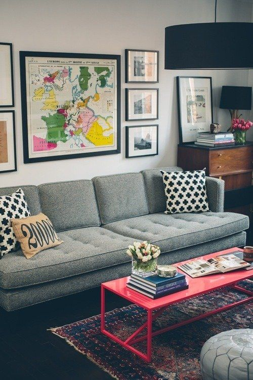This modern living room has an eclectic feel with a gray tufted sofa, red coffee table and wooden chest