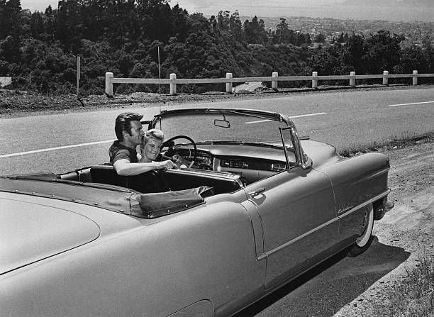 American actor Clint Eastwood with his first wife Maggie Johnson in a Cadillac convertible USA circa 1960