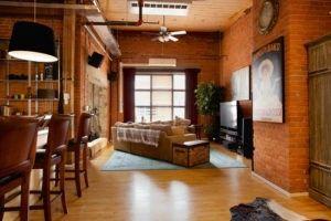 Diese industriellen Wohnzimmer verfügt über warme Rottöne von Herbst bis zur Decke und mit seinen unverputzten Ziegelwänden. Foto von AMR Innenarchitektur & Ausarbeitung Ltd.