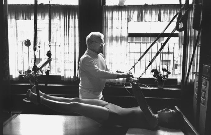 """Joseph Pilates enseñando respiración en el """"Cadillac"""" (o Trapecio)."""