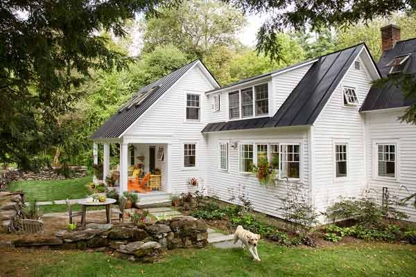 Shown: While honoring the home's historic style, she renovated the front and the back, with new windows and skylights and a porch facing a landscaped yard accented by salvaged stone walls.