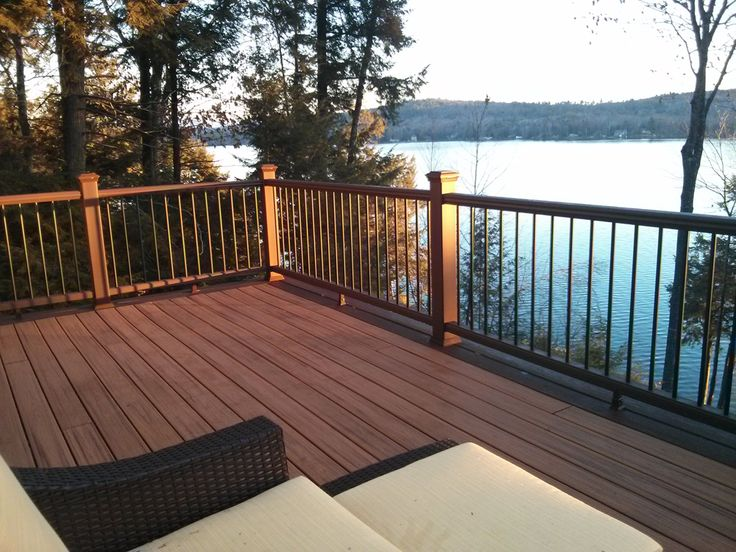 """Building industry influencer Tim Carter of """"Ask the Builder"""" recently remodeled his lakefront deck in New Hampshire using Trex Transcend decking in Tiki Torch and Lava Rock, along with Trex Transcend railing, Trex Deck Lighting and Trex RainEscape. This picturesque new deck looks like the perfect spot to watch a sunrise! #outdoorliving #backyard #deck #patio #porch"""