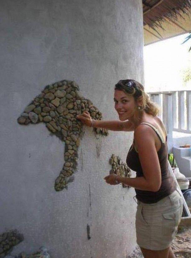 Met cement en stenen of mozaïek een muur versieren