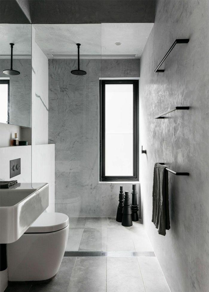 baldosas baño de color gris y negro con ventana larga de color negro, toalla ne…