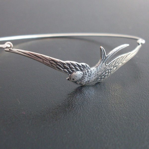 A brass sparrow in an antique silver finish spreading his wings wide has been transformed into a delicate bangle with silver filled band.    This stac