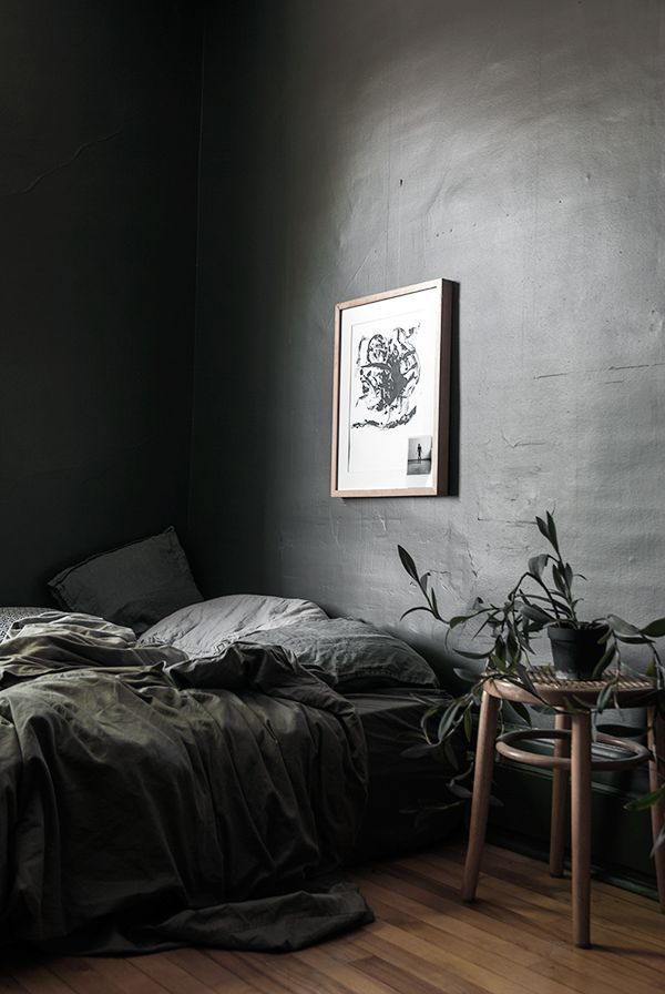 An unconventional dark grey bedroom. Dark colours allow the brain to relax into sleep better, so it might just work!
