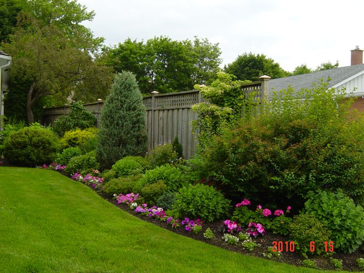 Flowers along the border and greenery along the fence make this backyard bed standout
