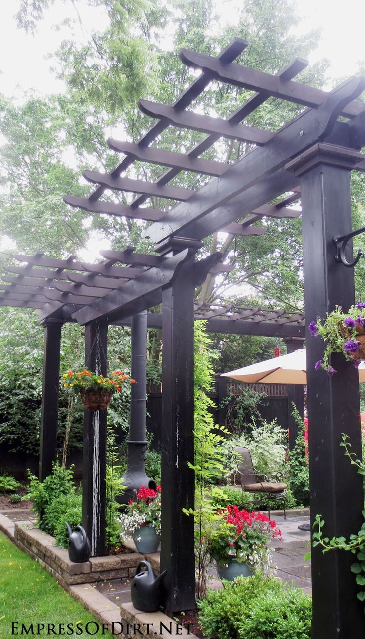 Wonderful modern style black arbor in back garden - see 20+ arbor, trellis, and obelisk ideas for your garden