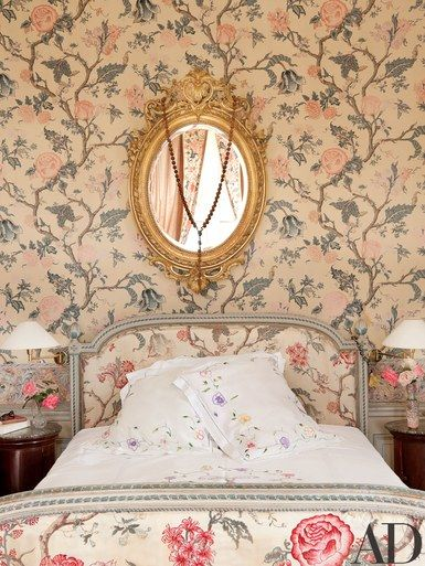 A gilt-wood mirror hangs above an 18th-century painted bed | archdigest.com