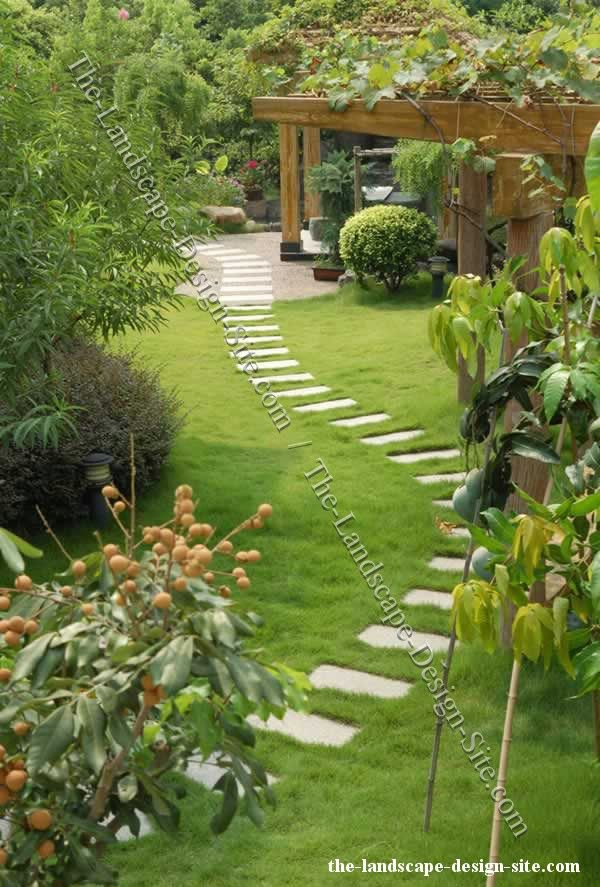 Large stepping stone path used in a lawn area that intersects with a gravel  bed area. Ideas for lawn paths and walkways.