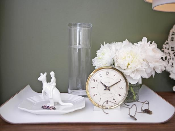 4 must-haves for guest room nightstand are a clock, a water carafe, a candle or flowers to add a pretty scent to the room and a tray or dish for guests to store their jewelry.