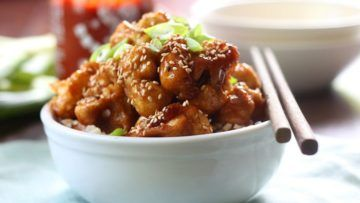 A delicious Asian-style recipe that is made of cauliflower florets which are dipped in a tasty batter and baked and afterwards tossed with a tasty sweet and spicy sesame sauce and served over rice. This vegan dish is packed with flavor, it's really simple to make and utterly delicious! #vegan #recipes #veganfood #cauliflower #dinner