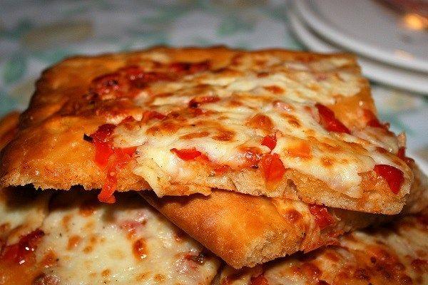 Pizza veloce in teglia con pomodorini e provolone, ha una metodica d'impasto in tre fasi che consente un ottimo risultato organolettico.