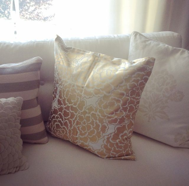 Gold, white, grey living room , Caitlin Wilson gold scallop pillow , dash and albert platinum and cream stripe pillow , Serena and lily pillows, pottery barn cream flower pillow, Ethan Allen white couch