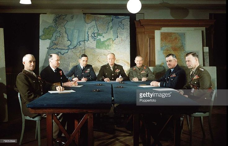 February 1944, World War II, The D Day Commanders, L-R; General Omar Bradley (1893-1981), Admiral Sir Bertram Ramsey, Air Chief Marshal Sir Arthur Tedder, General Dwight D. Eisenhower, General Sir Bernard Montgomery, Air Chief Marshal Sir Trafford Leigh Mallory, Lieutenant General Walter Bedell Smith all seated around a table planning the Allied invasion and liberation of Europe from Nazi occupation