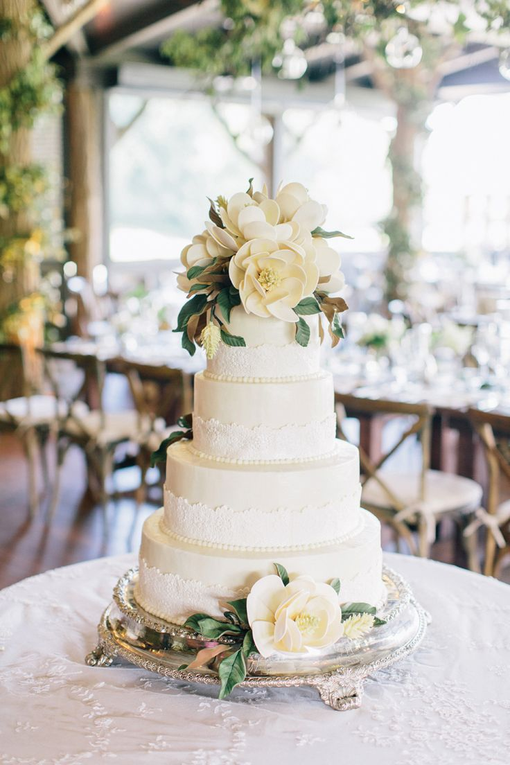 Wedding cake with magnolia blooms by Kathy Allen Fine Cakes, image by Corbin Gurkin. See more in the Spring 2014 issue of Weddings Unveiled.