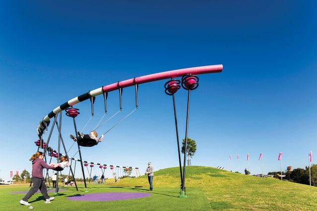 A semicircular swing set parallels the nearby grass mound. Image: Brett Boardman An energising playground at Sydney Olympic Park by JMD Design uses moulded terrain and supersized equipment to bring challenge and fun back to the park.  The recent opening of the final stage of the Blaxland Riverside Playground regional playspace heralds another major step in the activation and consolidation of the northern part of the park and the Newington Armory arts precinct, both in Sydney Olympic Par
