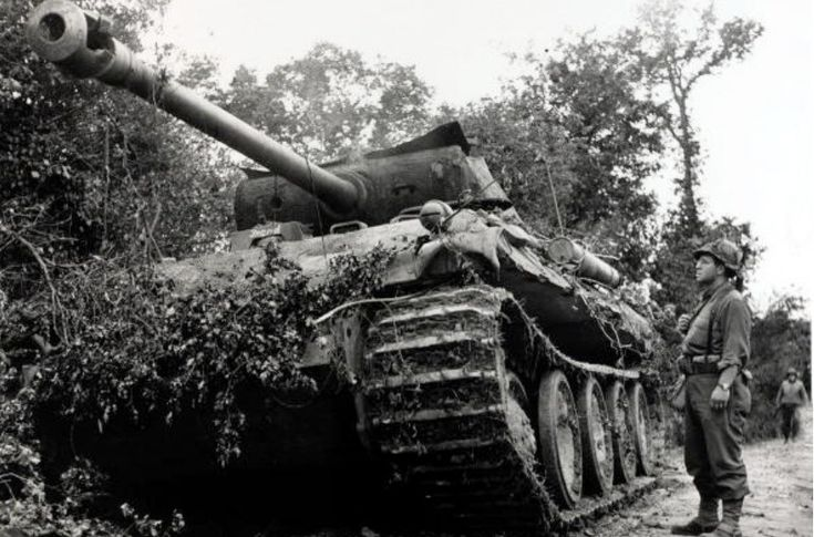 : 13th July 1944. A destroyed German Panther tank is inspected by an American soldier in the St.Lo - St.Jean de Daye area of France