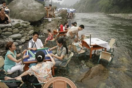 People playing Mahjong at river's edge during the hot summer. It must have been really hot.  Chengdu.