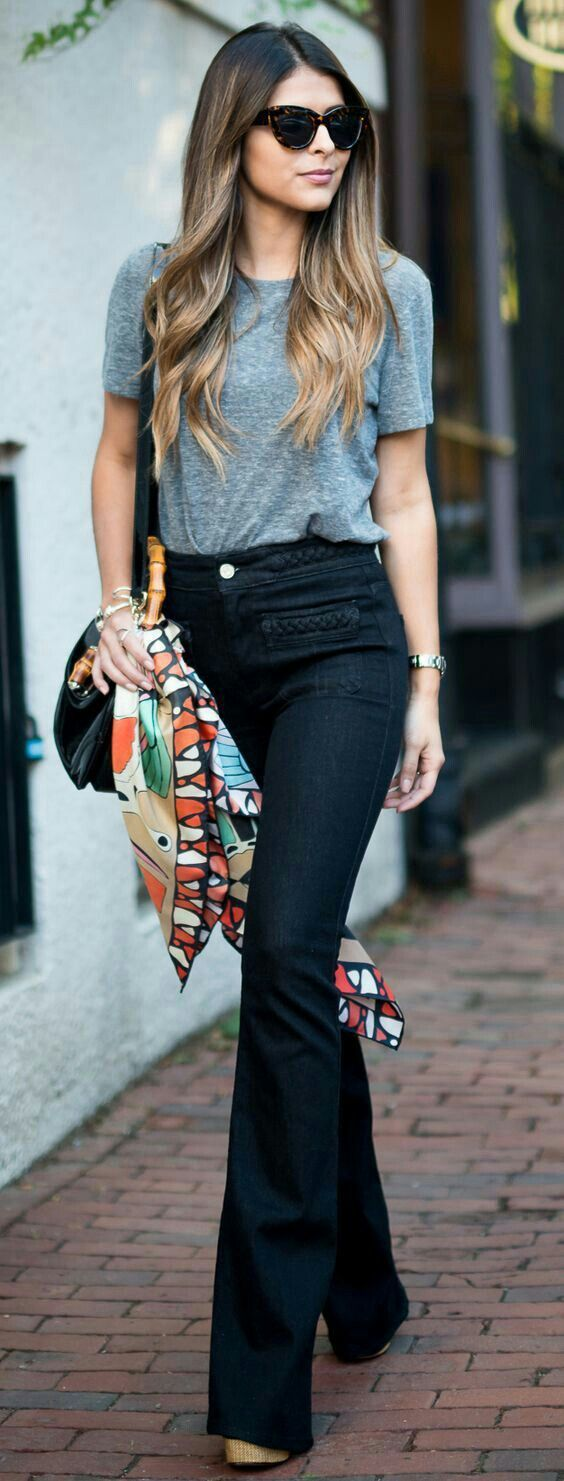 Simple. Gray tee worn with dark indigo wash jeans (can read black) and platform espadrilles. Oversized sunnies, black shoulder bag and colorful patterned scarf tied around it. Watch, bracelets. Minus the scarf it is minimalism personified. Style Planet