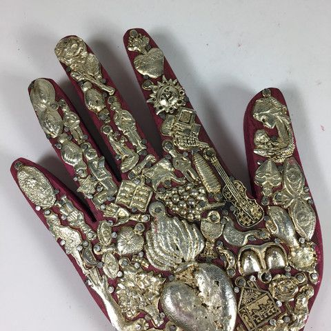 """A stained wooden hand covered with milagros. The larger hand needs to hang on the wall or lie flat due to the weight of the central sacred heart milagro. Each collection of pot metal milagros is one of a kind. The word """"milagro"""" means """"miracle"""" and they are small religious"""