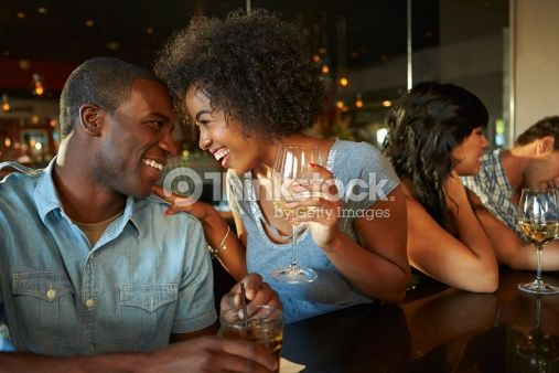 Stock Photo : Couple Enjoying Drink At Bar With Friends