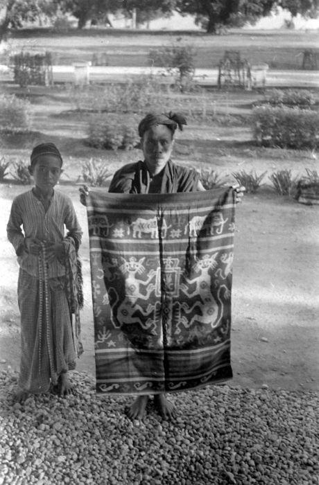 COLLECTIE TROPENMUSEUM Verkoper met een heupdoek met het Nederlandse wapen te Waingapu op Oost-Sumba.