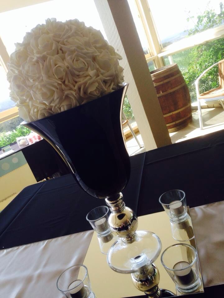 Stunning kissing ball in a black and silver vase.