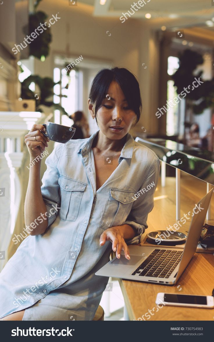 Attractive asian woman is surfing the web on her portable
